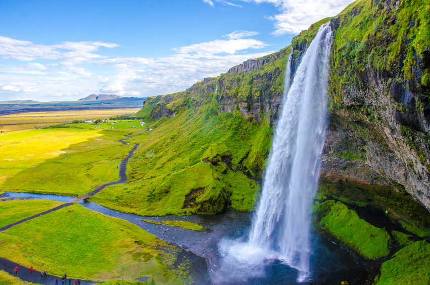 Panoramic view of the idyllic Seljalandsfoss waterfall on a sunny day in summer.